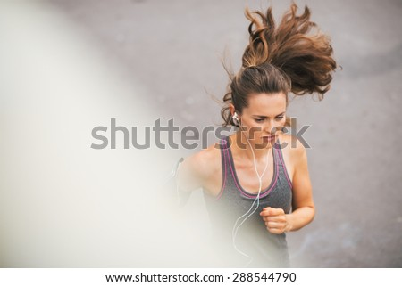 A woman jogger is running, concentrated and in the zone as she listens to music on her earbuds. - stock photo