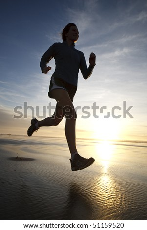 A woman jogging along a sandy beach. - stock photo