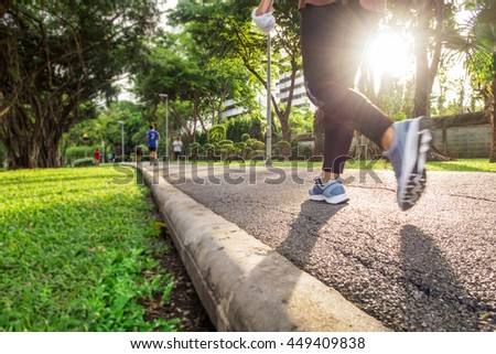 A woman jogging in the park beside the lake ,in the evening light , (from below angle view) - stock photo