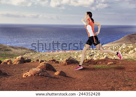 a woman jogging on the rocky coast trail - stock photo