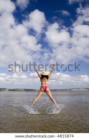 a woman jumping with her hat at the beach (motion blur)