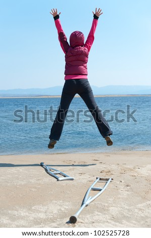 a woman jumps, having left her crutches, at a lake shore, back view - stock photo