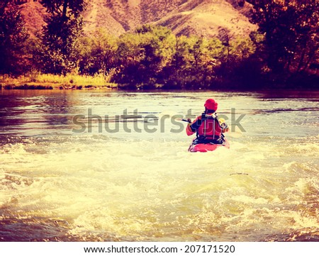a woman kayaking on a rough river during fall toned with a retro vintage instagram filter  - stock photo