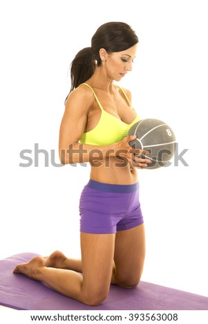 a woman kneeling on her mat, with a medicine ball in her hands.