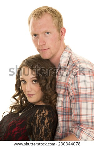 A woman laying back in her man;s arms looking. - stock photo