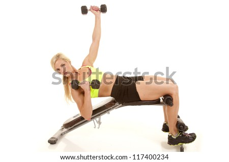 A woman laying back on a bench working her abs and arms with weights. - stock photo