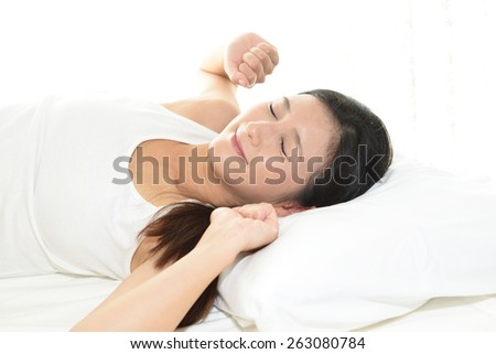 A woman laying down on the bed - stock photo