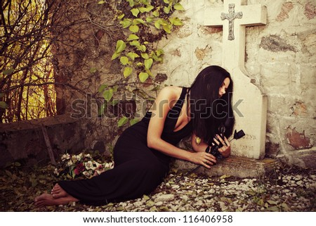 a woman laying in front of grave stone - stock photo