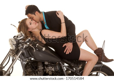 A woman  laying on her a motorcycle and her man is going in for a kiss on her cheek. - stock photo