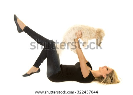 a woman laying on her back holding up her puppy. - stock photo