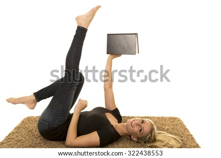 a woman laying on her carpet reading a book with a smile on her face.
