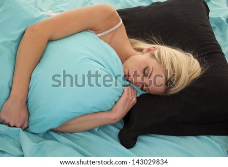 a woman laying on her pillow covered by another pillow asleep - stock photo