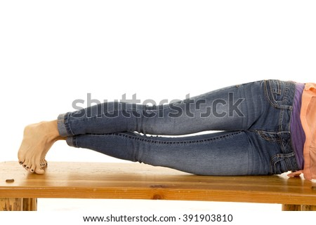 A woman laying on her side on her bench, with her toes on the bench.