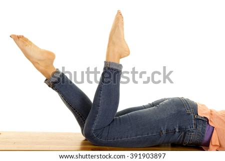 A woman laying on her stomach with her feet kicked up.