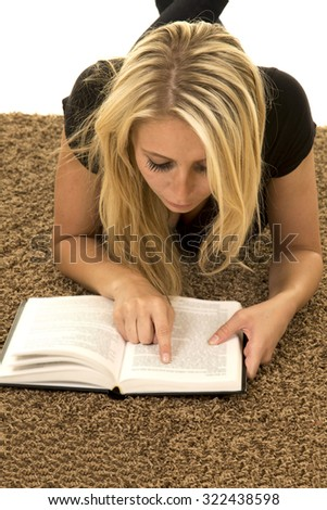 a woman laying on the carpet reading her book. - stock photo