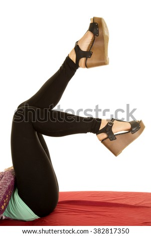 a woman laying with her feet up, with her heels on. - stock photo