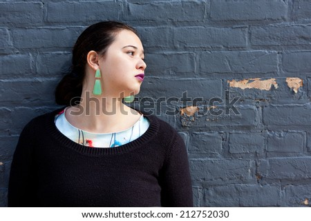 A woman leaning against a brick wall looking away. - stock photo