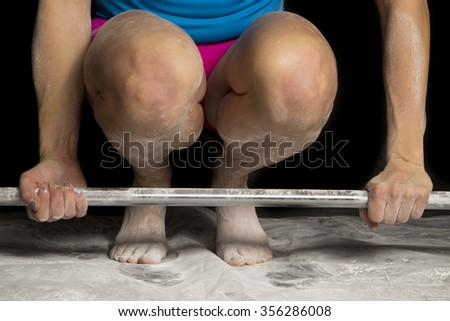 A woman leaning down, preparing for a dead lift. - stock photo