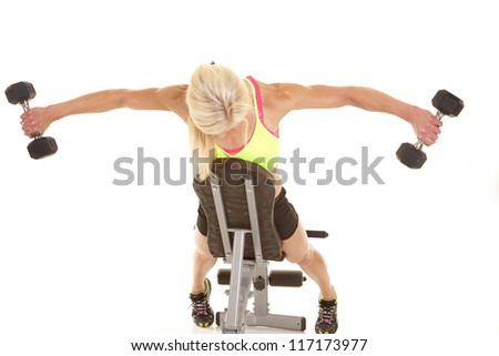 a woman leaning on a bench doing a fly lift with weights.