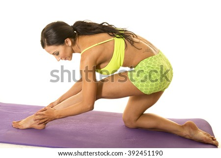 a woman leaning over stretching out her legs.