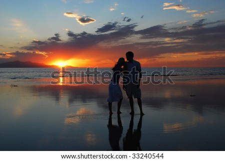A woman leans on a man's shoulder during as they watch the sunset - stock photo