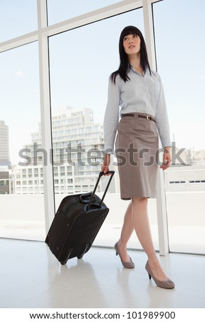 A woman leaving her office with a suitcase in hand - stock photo