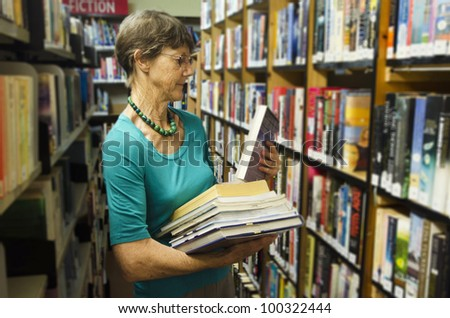 A woman librarian holds books beside bookshelf in library. - stock photo