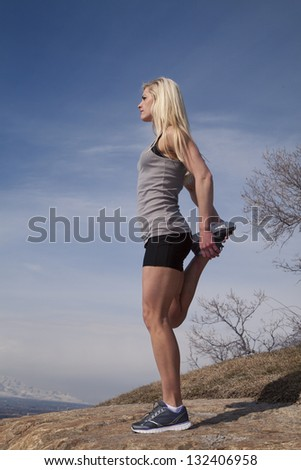 A woman lifting up her leg to stretch in the outdoors.