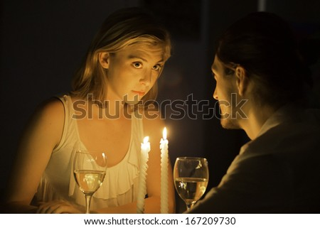 A woman listens intently as she gazes across at her partner as they sit at a candle lit table and drink white wine. - stock photo
