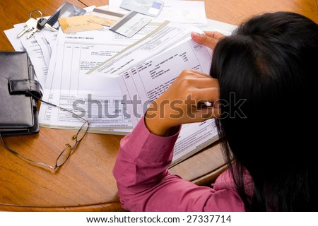 A woman looked so stress looking at credit card's bill all other debt invoice. - stock photo