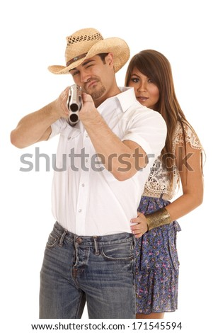 A woman looking around her cowboy as he is getting ready to shoot a gun - stock photo