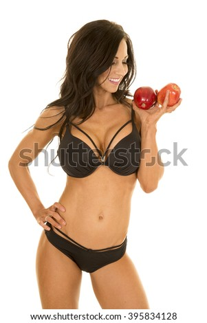 a woman looking at her apples with a smile in her bikini.