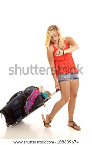A woman looking at her watch with a shocked expression on her face with her suitcase overflowing with clothes. - stock photo