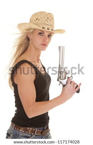 A woman looking at the camera holding a gun with a serious expression on her face wearing her cowgirl hat. - stock photo