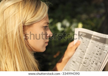 A woman looking at the job listings in the newspaper. Focus is on the woman. - stock photo