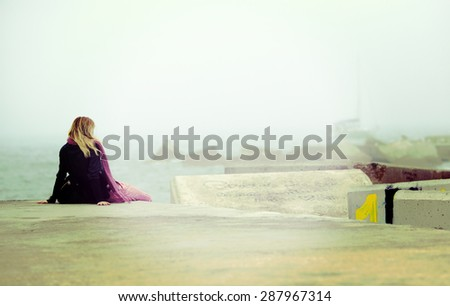 A woman looking at the sea and wondering about the past. Image has a vintage effect. - stock photo