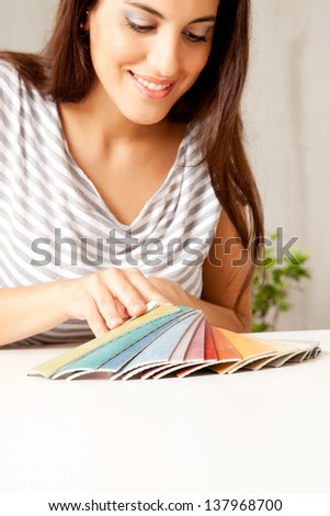 A woman looking at various flooring color swatches - stock photo