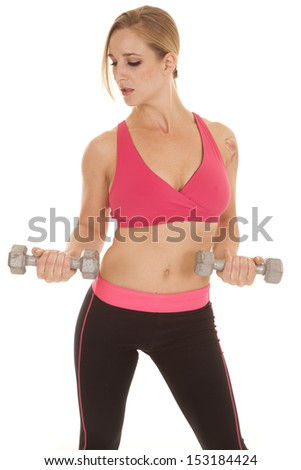 A woman looking down and curling weights.