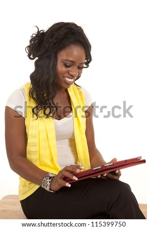 A woman looking down at her electronic tablet with a smile on her face