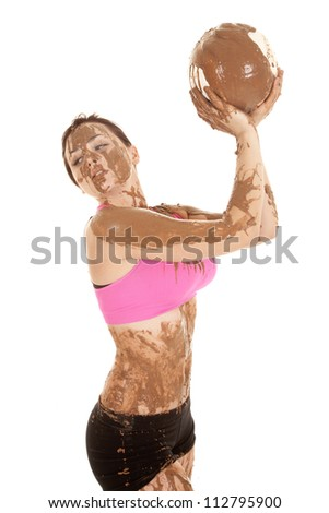 A woman looking over her shoulder holding up a volleyball that is covered in mud - stock photo
