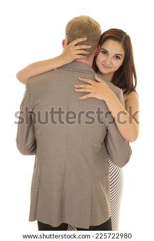 A woman looking over the shoulder of her man with a small smile on her face. - stock photo