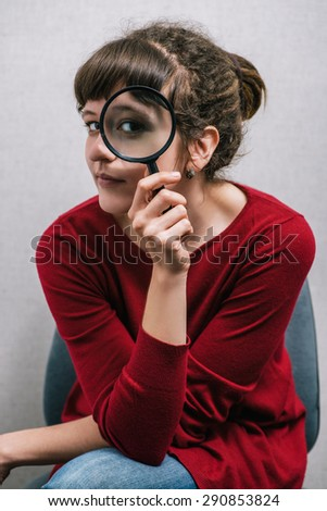 A woman looking through a magnifying glass. On a gray background. - stock photo
