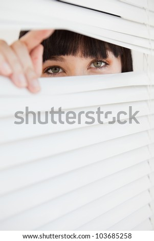 A woman looking through a set of closed blinds by opening a part with her fingers - stock photo