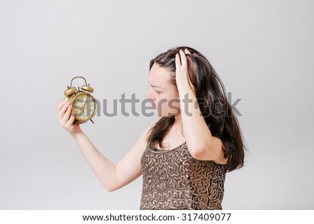 A woman looks at a wall clock with a hand on his head. On a gray background.