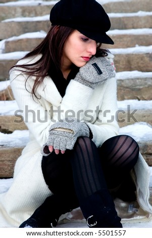 A woman lost in her thoughts sits on the snowed over steps