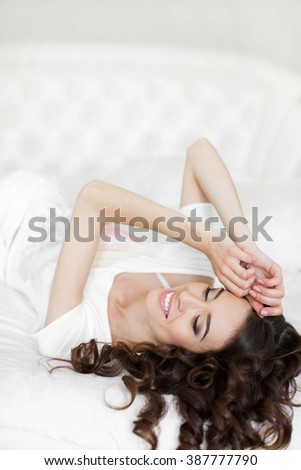 A woman lying at the end of the bed underneath the quilt and smiling, with her head resting upon her hand with the other in her hair. young beautiful girl in a bed. Sensual woman lying in bed - stock photo