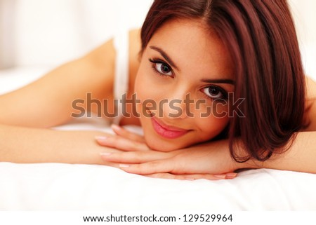 A woman lying on the bed and smiling - stock photo