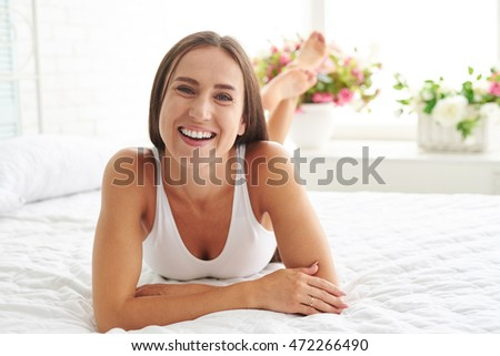 A woman lying on the bed looking forward and smiling while enjoying a carelessness morning at home