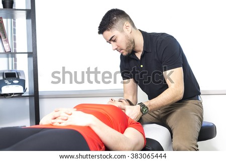 A woman lying while being massaged by a man in a room - stock photo