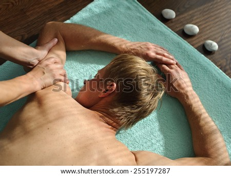 A woman makes a man a massage. She massages her shoulders